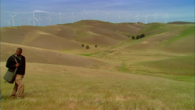 ws woman + two businessmen holding rolled plans and surveying landscape near wind turbines on hill / livermore, california, usa - ansvarsfullt företagande bildbanksvideor och videomaterial från bakom kulisserna