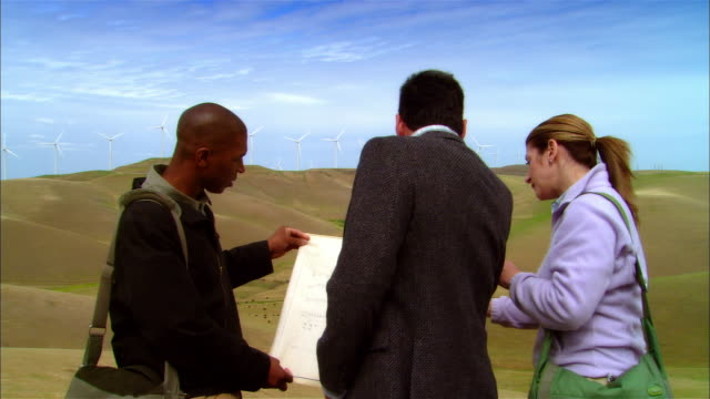 ms woman + two businessmen reading plans and pointing to wind turbines on hill / livermore, california, usa - female with group of males stock videos & royalty-free footage