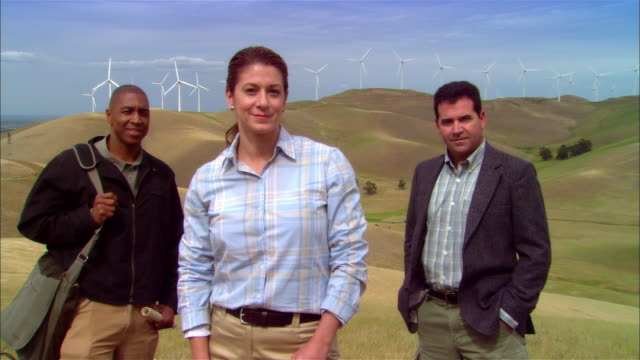 MS PAN Woman + two businessmen standing in field near wind turbines on hill / Livermore, California, USA
