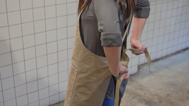 woman tying an apron for working - apron stock videos & royalty-free footage