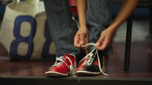 vídeos de stock, filmes e b-roll de cu woman tying bowling shoes, low section / dover, new hampshire, usa - sapato de boliche