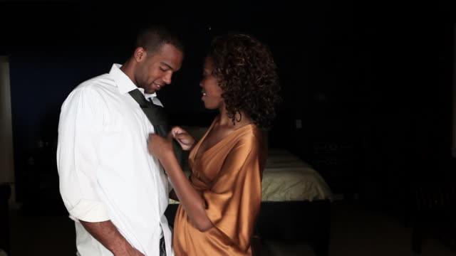 Woman tying boyfriend's tie and kissing him