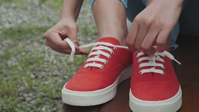 woman tying  canvas shoes - tighten stock videos and b-roll footage