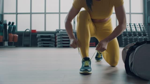 stockvideo's en b-roll-footage met vrouw die haar oefeningsschoenen bindt - bodybuilding