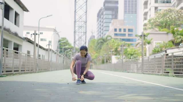 stockvideo's en b-roll-footage met woman tying her exercise shoes - jogster