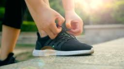 Woman tying her sports shoe