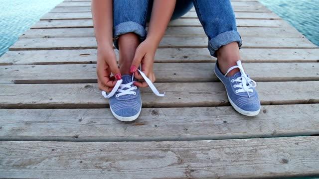 woman tying shoelace on wooden boardwalk seaside - shoelace stock videos and b-roll footage