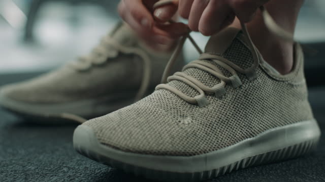woman tying shoelaces of sneakers - trainer stock videos & royalty-free footage
