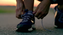 SLO MO Woman tying shoelaces on running shoes