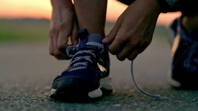 vídeos de stock e filmes b-roll de slo mo woman tying shoelaces on running shoes - preparação