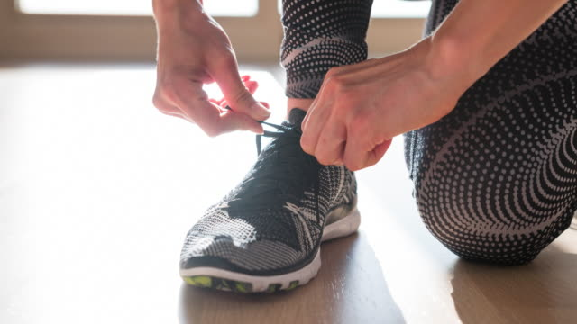 woman tying shoelaces on sports shoe - aerobics stock videos & royalty-free footage