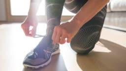 Woman tying shoelaces on sports shoe
