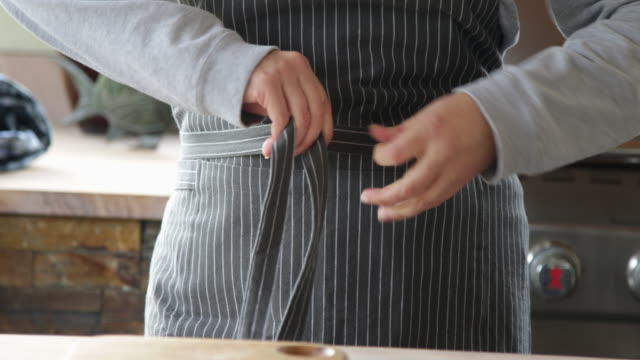 cu woman tying up apron - apron stock videos & royalty-free footage