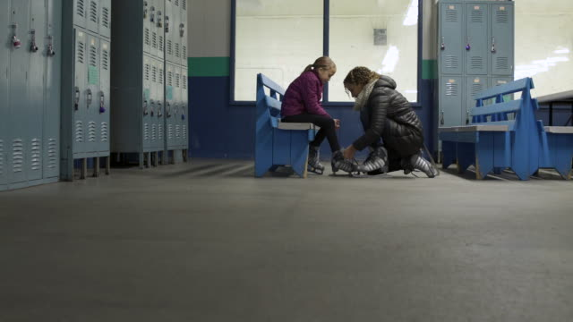 Woman tying young girls ice skates.