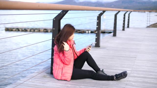 vidéos et rushes de femme tape un message sur son téléphone - neige fraîche