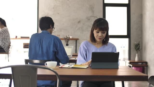 stockvideo's en b-roll-footage met vrouw in café te typen op tablet pc - tablet pc