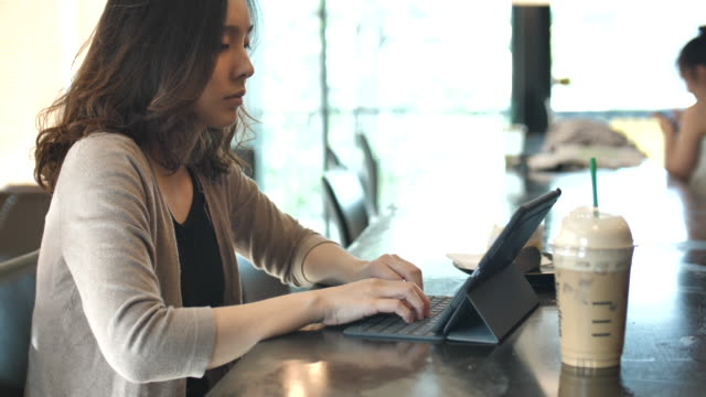 Woman typing at Tablet PC in cafe