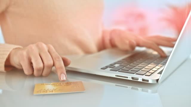 vídeos de stock, filmes e b-roll de slo mo mulher digitando suas informações de cartão de crédito no laptop - gastando dinheiro