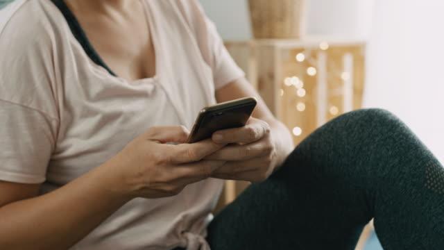 vídeos de stock, filmes e b-roll de ds mulher digitando em um telefone inteligente em casa - só uma mulher de idade mediana