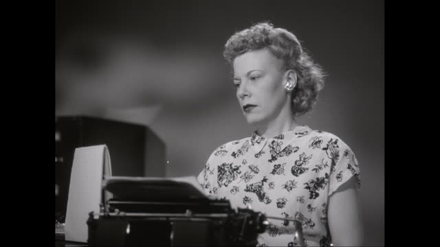 MS Woman typing on antique typewriter in office / United States