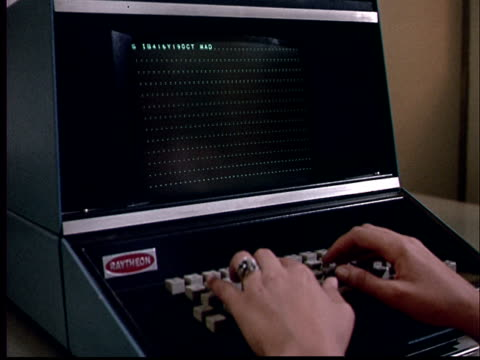 1970 MS Woman typing on computer/ CU Finger pushing button/ CU Black screen w/ green text