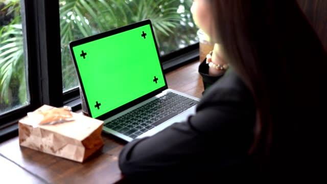 vídeos de stock, filmes e b-roll de mulher digitando no computador do laptop do teclado e tela verde - espaço vazio