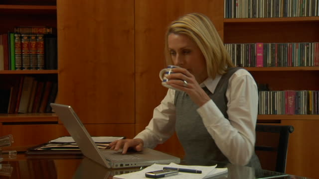 vidéos et rushes de ms pan woman typing on laptop and drinking from mug in study / london, england - main au menton