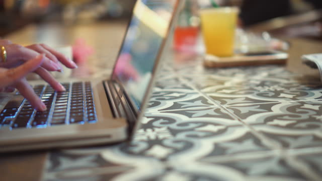 woman typing on laptop keyboard in coffee shop,dolly shot - shift key stock videos & royalty-free footage