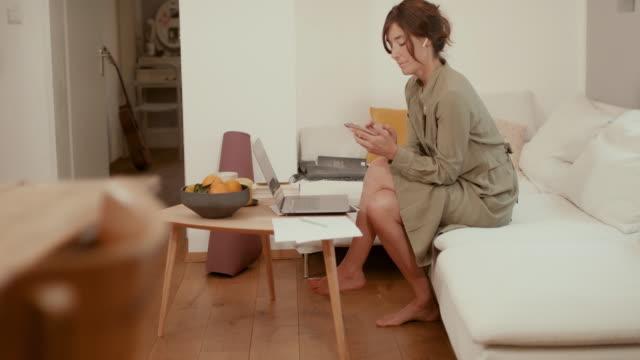 woman typing on laptop, talking on phone, drinking tea on sofa - mug stock videos & royalty-free footage