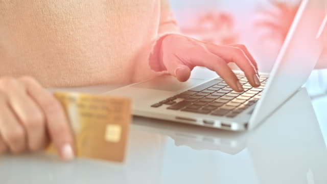SLO MO woman typing on laptop while holding credit card