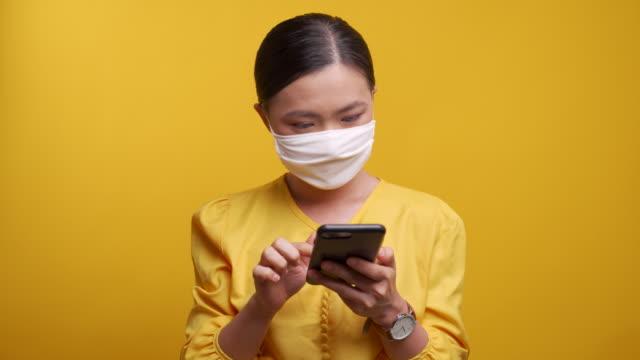 vidéos et rushes de femme tapant le téléphone intelligent au-dessus du fond jaune - intelligence