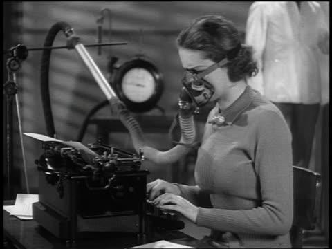 stockvideo's en b-roll-footage met b/w 1937 ms profile woman typing + wearing oxygen mask / man in white coat in background - secretaris