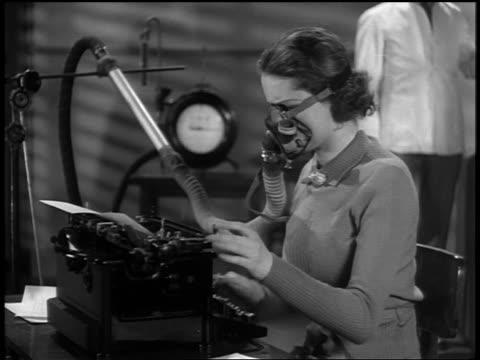 b/w 1937 ms profile woman typing + wearing oxygen mask / man in white coat in background - 1937年点の映像素材/bロール