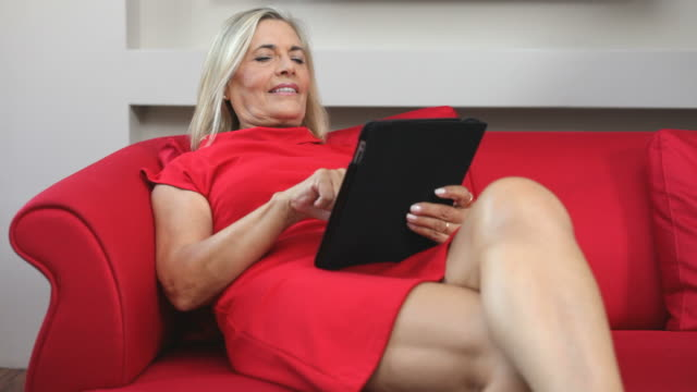 woman typing with digital tablet on red sofà - human limb stock videos & royalty-free footage