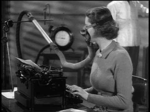b/w 1937 ms profile woman typing with oxygen mask turns, looks at scientist + takes deep breath - 1937年点の映像素材/bロール