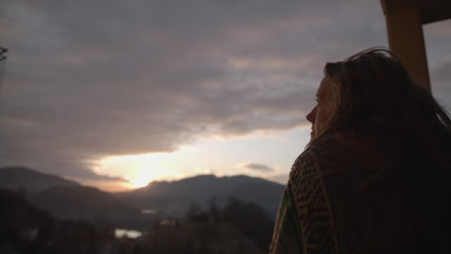 woman under blanket looks out over railing at view of sunset and mountains - stare in piedi video stock e b–roll