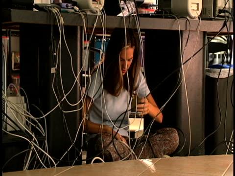 vídeos y material grabado en eventos de stock de woman under computer desk - encuadre de tres cuartos