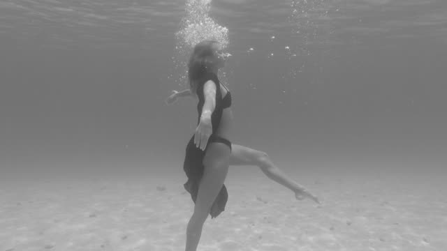 a woman underwater swimming dancing in a bikini over a coral reef. - slow motion - etereo video stock e b–roll