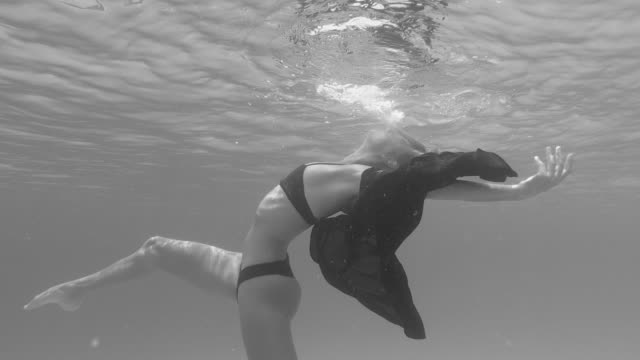 a woman underwater swimming dancing in a bikini over a coral reef. - slow motion - black and white stock videos & royalty-free footage