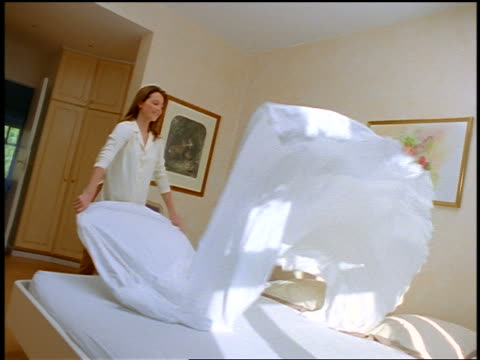 woman unfolding white sheet over bed + making bed - making stock videos & royalty-free footage