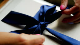 woman unleashes a blue bow