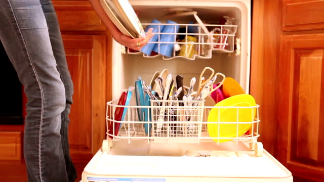 stockvideo's en b-roll-footage met woman unloading a dishwasher - lossen