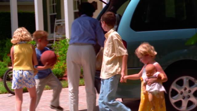 vidéos et rushes de pan woman unloading groceries from minivan in driveway + giving them to children / florida - famille avec quatre enfants