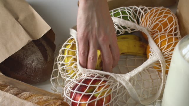 vídeos de stock e filmes b-roll de woman unloading her fresh groceries she got on a kitchen counter - saco objeto manufaturado