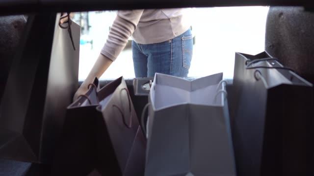 vídeos de stock, filmes e b-roll de mulher descarrega as compras em sacos no carro dela - sacola de compras