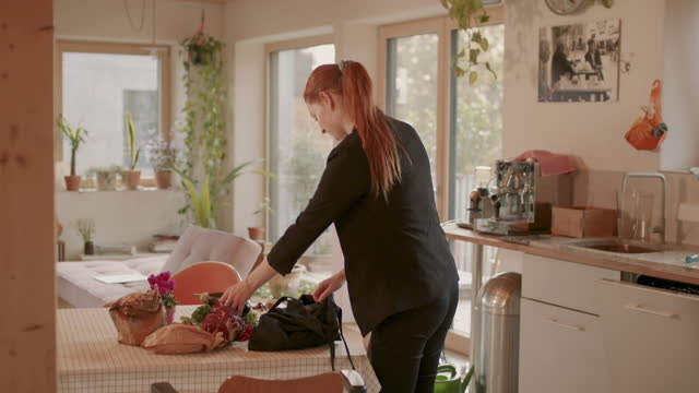 woman unpacking bag of groceries at kitchen table - arrival stock videos & royalty-free footage