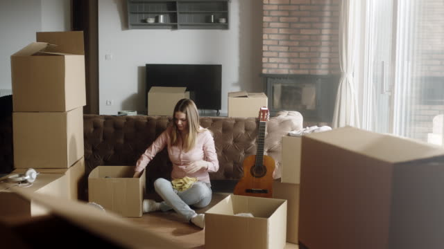 Woman unpacking boxes at new house