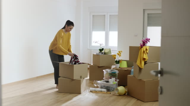 woman unpacking cardboard boxes in her new apartment - new stock videos & royalty-free footage