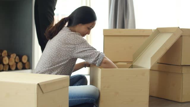 vídeos de stock, filmes e b-roll de mulher de descompactação de caixa de papelão para nova casa - mudar de casa