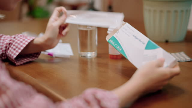 woman unpacking rapid antigen test kit at home. - rapid stock videos & royalty-free footage